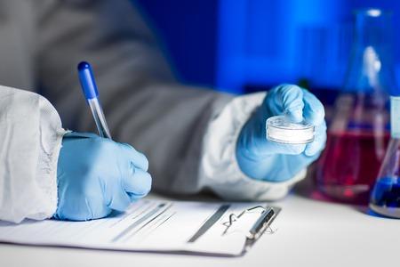 wetenschap, chemie, medicijnen en mensen concept - close-up van jonge wetenschapper met een monster van chemische stof die nota's over klembord en het maken van test of een onderzoek in het laboratorium