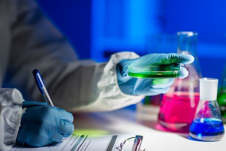 laboratory technician: science, chemistry, medicine and people concept - close up of young scientist with chemical sample taking notes on clipboard and making test or research in laboratory Stock Photo