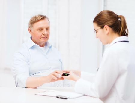 blood sugar level: healthcare, elderly and medical concept - female doctor or nurse with patient measuring blood sugar value