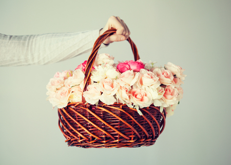 hand basket: close up of mans hand holding basket full of flowers. Stock Photo