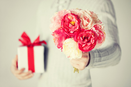 close up of man holding bouquet of flowers and gift box. photo