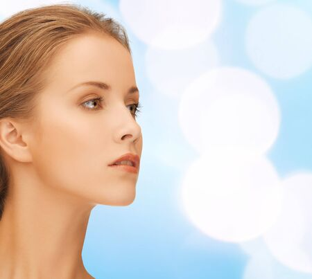 side light: beauty, people and health concept - beautiful young woman face over blue lights background