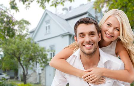 abrazar familia: concepto de amor, las personas, los bienes ra�ces, el hogar y la familia - la sonriente pareja abrazando sobre fondo de la casa