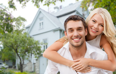 real estate background: love, people, real estate, home and family concept - smiling couple hugging over house background