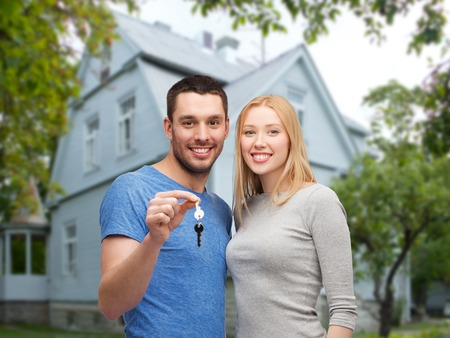 nice accommodations: love, people, real estate, home and family concept - smiling couple showing key over house background