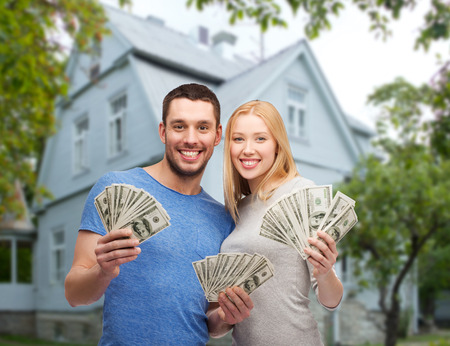 win money: love, people, real estate, home and family concept - smiling couple showing dollar cash money over house background
