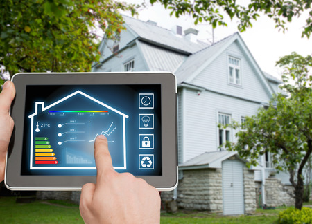 home, housing, people and technology concept - close up of man hands pointing finger to tablet pc computer and regulating room temperature over house background Foto de archivo
