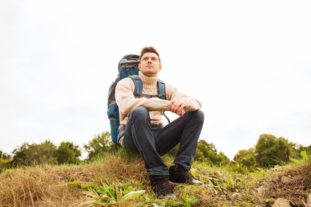 sitting on the ground: adventure, travel, tourism, hike and people concept - man with backpack sitting on ground Stock Photo