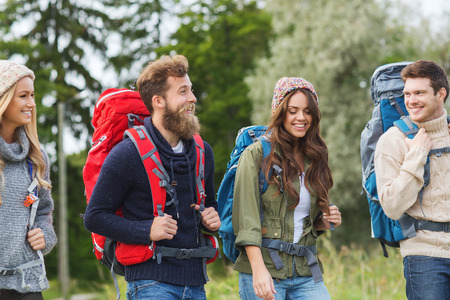trekking: adventure, travel, tourism, hike and people concept - group of smiling friends walking with backpacks Stock Photo