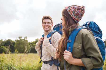 tourism: adventure, travel, tourism, hike and people concept - smiling couple walking with backpacks outdoors
