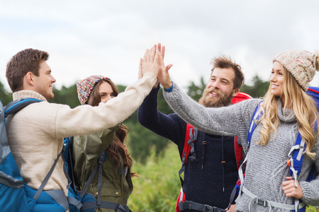 high: travel, tourism, hike, gesture and people concept - group of smiling friends with backpacks making high five outdoors