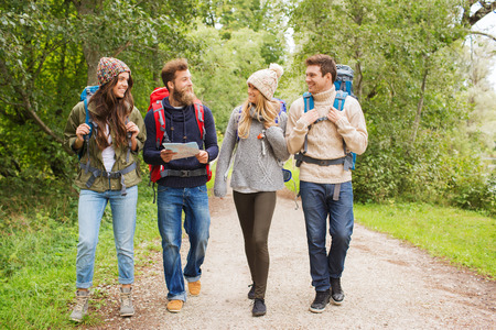 outdoor activities: adventure, travel, tourism, hike and people concept - group of smiling friends with backpacks and map walking outdoors Stock Photo