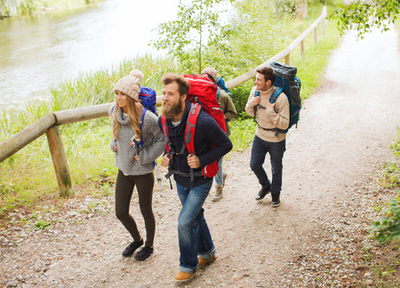 adventure sports: adventure, travel, tourism, hike and people concept - group of smiling friends walking with backpacks Stock Photo