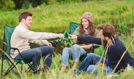 adventure, travel, tourism, friendship and people concept - group of smiling tourists clinking beer bottles in camping photo