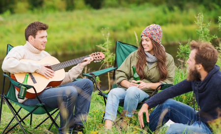 adventure, travel, tourism and people concept - group of smiling tourists playing guitar and drinking beer in camping photo
