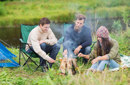 campfire: adventure, travel, tourism and people concept - group of smiling friends with marshmallow sitting around bonfire in camping Stock Photo