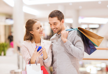 sale, consumerism, technology and people concept - happy young couple with shopping bags and smartphone talking in mall Фото со стока