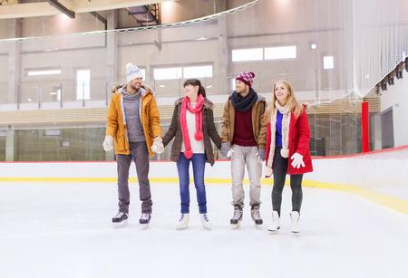 patinando: la gente, la amistad, el deporte y el concepto de ocio - amigos felices en pista de patinaje