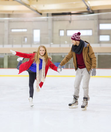 iceskates: people, friendship, sport and leisure concept - happy couple holding hands on skating rink