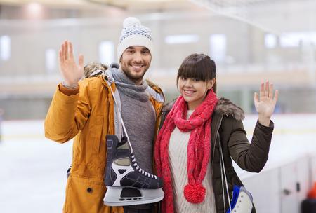 patinaje sobre hielo: la gente, la amistad, el deporte y el concepto de ocio - pareja feliz con patines de hielo en la pista de patinaje