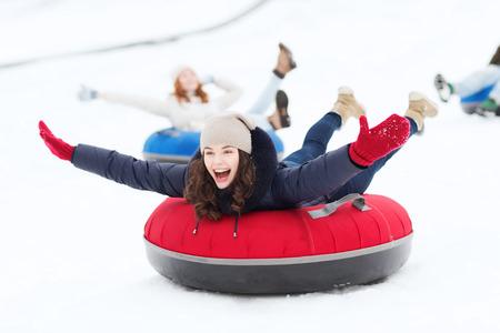 Inverno, tempo libero, sport, l'amicizia e la gente concetto - gruppo di amici felici scivolare sulla neve tubi Archivio Fotografico - 36052502