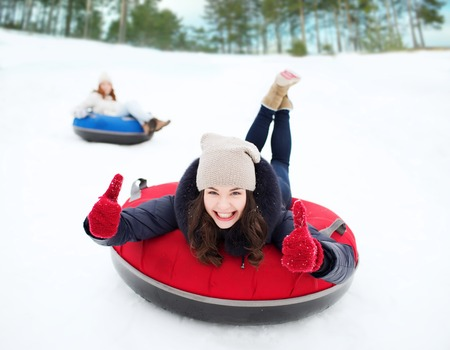 winter, leisure, sport, friendship and people concept - group of happy friends sliding down on snow tubes photo