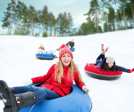 woman fashion: winter, leisure, sport, friendship and people concept - group of happy friends sliding down on snow tubes