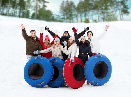 winter, leisure, sport, friendship and people concept - group of smiling friends with snow tubes waving hands outdoors Reklamní fotografie