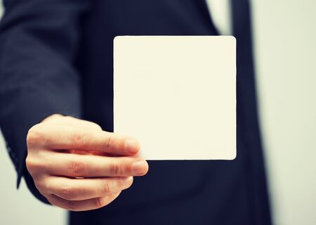 picture of man in suit holding blank card photo