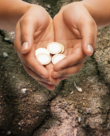 starvation: poverty, starvation, ecology and charity concept - closeup of female hands holding euro coins over ground background