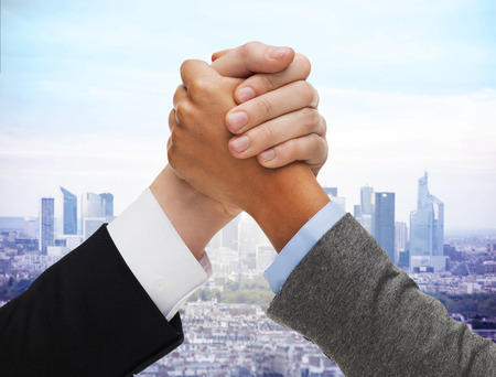 business competition, challenge, cooperation, people and partnership concept - concept - close up of hands arm wrestling over city background photo