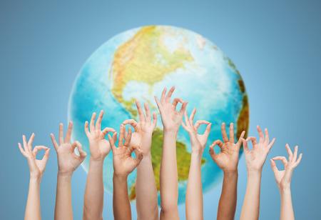 paz: gesto, as pessoas, a humanidade ea comunidade conceito - mãos humanas mostrando sinal de ok sobre o globo da terra e fundo azul