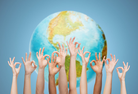 populations: gesture, people, humanity and community concept - human hands showing ok sign over earth globe and blue background