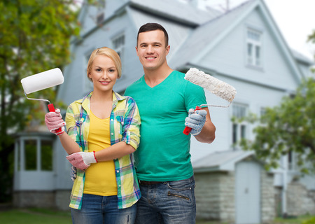 renovation property: repair, people, real estate, home and family concept - smiling couple with paint rollers over house background