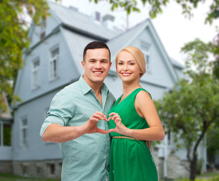 love, people, real estate, home and family concept - smiling couple hugging and showing heart shape gesture over house background