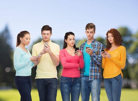 friendship, technology and people concept - group of serious teenagers with smartphones over park background photo