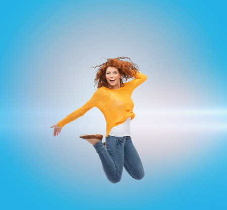 air movement: happiness, freedom, movement and people concept - smiling young woman jumping in air over blue laser background Stock Photo