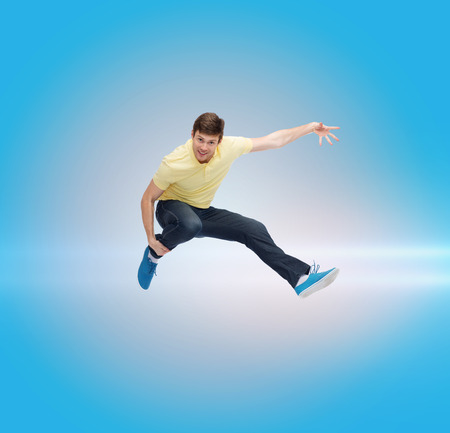 air movement: happiness, freedom, movement and people concept - smiling young man jumping in air over blue laser background