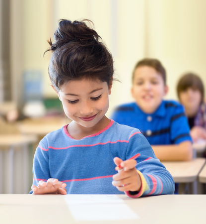 learners: education, elementary school and children concept - happy little student girl with pen and paper writing over classroom and classmates background Stock Photo