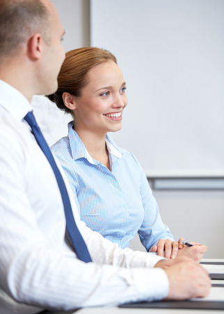 happy businesswoman: business, people and teamwork concept - smiling businessman and businesswoman meeting in office