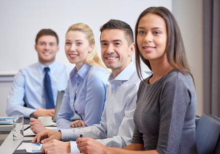 personas sentadas: negocio, la gente y el concepto de trabajo en equipo - grupo de sonriente de reuni�n de empresarios en la presentaci�n en la oficina Foto de archivo