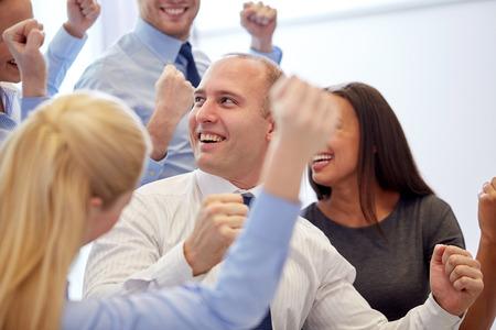 mujer trabajadora: negocio, trabajo en equipo, la gente y el concepto de �xito - sonriente equipo de negocios haciendo el gesto de triunfo en la oficina