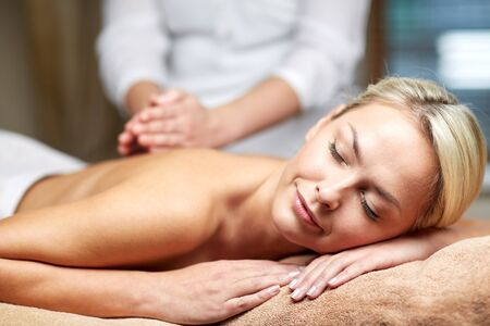 therapeutic: people, beauty, spa, healthy lifestyle and relaxation concept - close up of beautiful young woman lying with closed eyes and having hand massage in spa