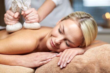 massaggio: persone, bellezza, spa, stile di vita sano e concetto di rilassamento - vicino di giovane e bella donna sdraiata e con massaggio sacchetto di erbe in spa
