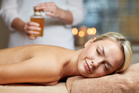 massagist: people, beauty, spa, healthy lifestyle and relaxation concept - close up of beautiful young woman lying with closed eyes on massage table and therapist holding oil bottle in spa