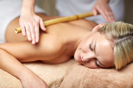 bamboo therapy: people, beauty, spa, healthy lifestyle and relaxation concept - close up of beautiful young woman lying with closed eyes and having bamboo massage in spa