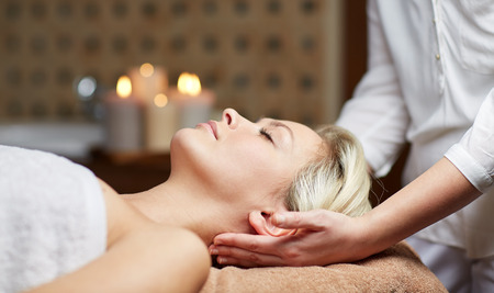 people relax: people, beauty, spa, healthy lifestyle and relaxation concept - close up of beautiful young woman lying with closed eyes and having head massage in spa