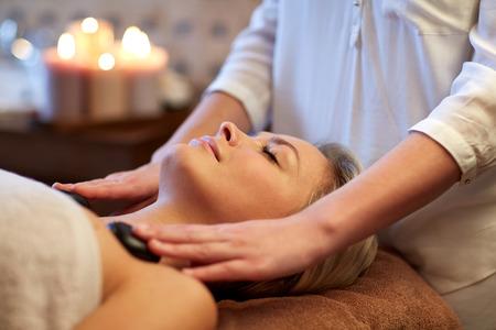 calor: personas, belleza, spa, estilo de vida saludable y la relajaci�n concepto - cerca de la hermosa mujer joven que tiene masaje con piedras calientes en el spa
