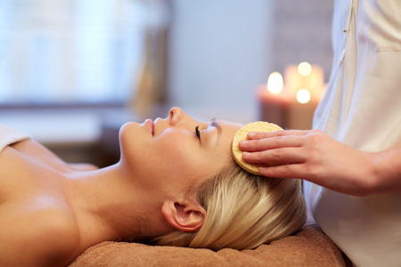 spa relax: people, beauty, spa, healthy lifestyle and relaxation concept - close up of beautiful young woman lying with closed eyes and having face massage with sponge in spa Stock Photo