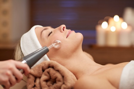 cosmetologies: people, beauty, spa, cosmetology and technology concept - close up of beautiful young woman lying with closed eyes having face massage by massager in spa